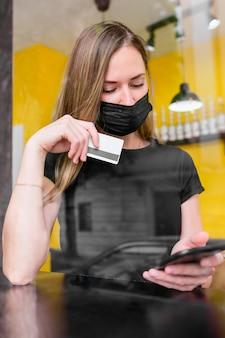 Volwassen vrouw die met gezichtsmasker online winkelt