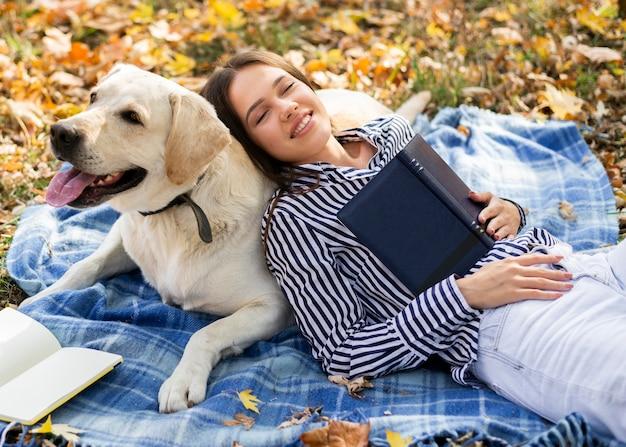 Volwassen vrouw die met haar hond speelt