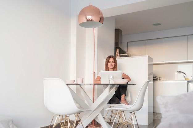 Volwassen vrouw die met laptop thuis werkt