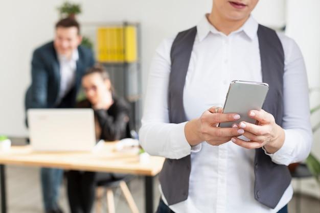 Volwassen vrouw die mobiele telefoon controleert