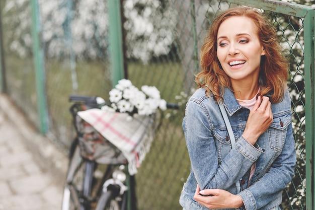 Volwassen vrouw die naast lentebloemen staat Gratis Foto