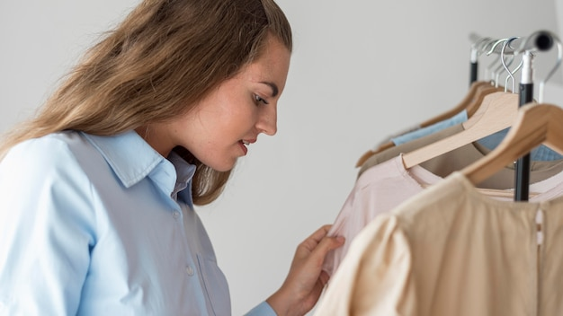 Volwassen vrouw die nieuwe kleren controleert