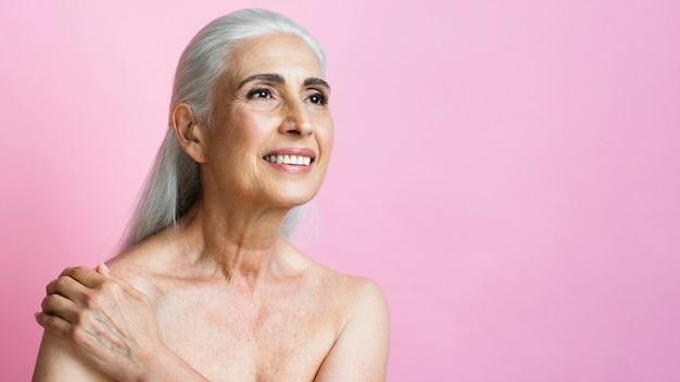Volwassen vrouw die op roze achtergrond glimlacht