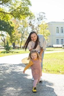 Volwassen vrouw die plezier heeft, haar kinddochter inhaalt in groen park.