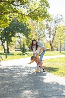Volwassen vrouw die plezier heeft met het inhalen van haar kinddochter in groen park
