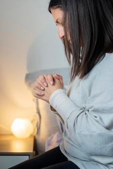 Volwassen vrouw die thuis bidt