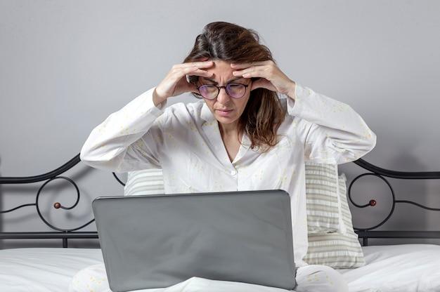 Volwassen vrouw die thuis in pijama werkt