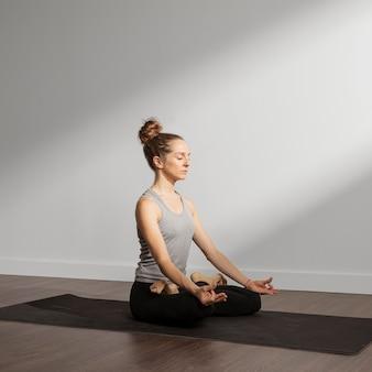 Volwassen vrouw die thuis mediteert
