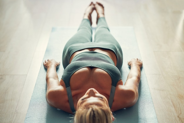 Volwassen vrouw die thuis yoga beoefent