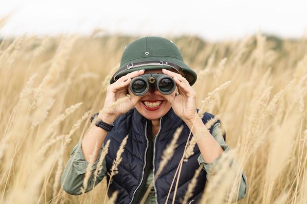 Volwassen vrouw die verrekijkers onderzoekt