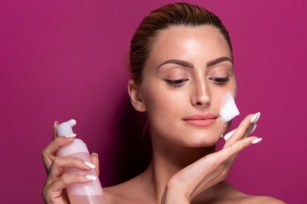 Volwassen vrouw die vochtinbrengende crème op haar gezicht toepast