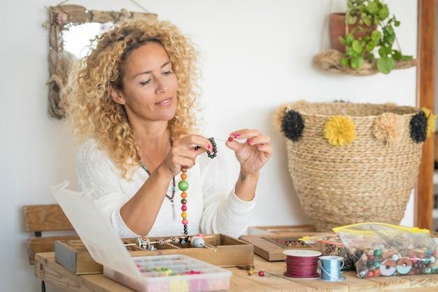 Volwassen vrouw doet handgemaakte sieraden thuis met kleurrijke kralen en koorden