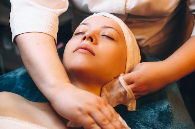 Volwassen vrouw doet ontspannende huidverzorgingsroutine in een wellness-kuuroord door een schoonheidsspecialist.