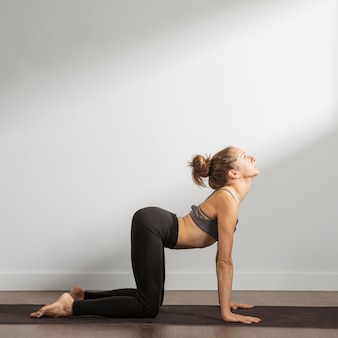 Volwassen vrouw doet yoga thuis