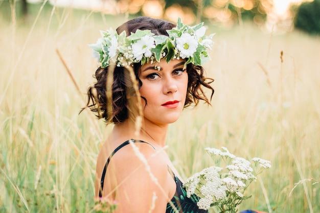 Volwassen vrouw draagt een gebloemde jurk met een bloemenkrans op haar hoofd en poseert in een veld