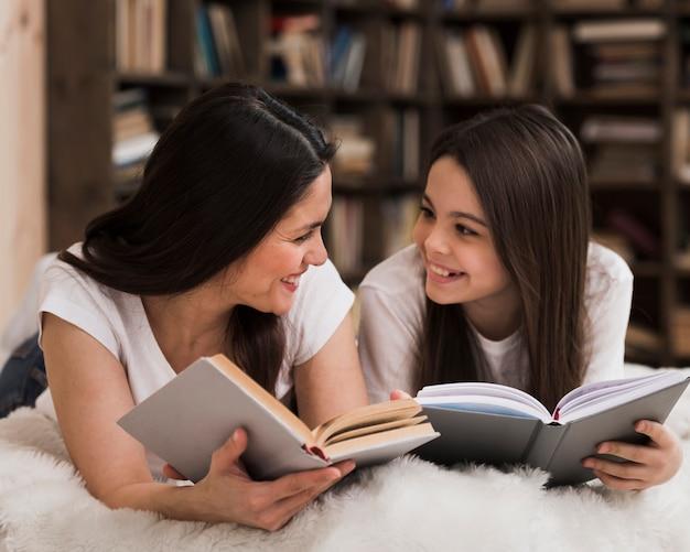 Volwassen vrouw en jong meisje die bij elkaar glimlachen