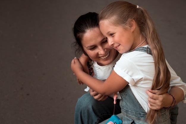 Volwassen vrouw en klein meisje moeder en dochter knuffelen geïsoleerd op grijs