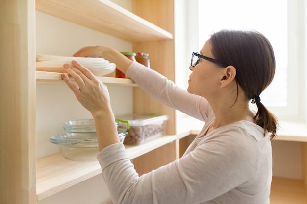 Volwassen vrouw het plukken voedsel van opslagkabinet in keuken