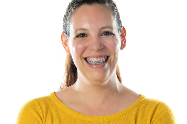 Volwassen vrouw in bretels draagt een gele trui geïsoleerd