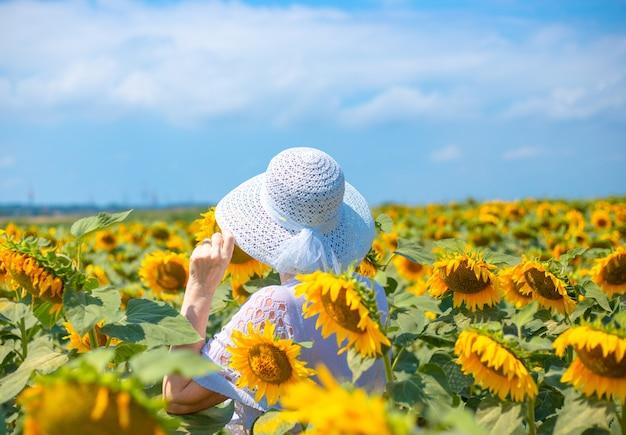 Volwassen vrouw in een hoed staat op een veld met bloeiende zonnebloemen en kijkt in de verte