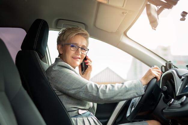 Volwassen vrouw in een pak met een telefoon in zijn hand in een auto rijden