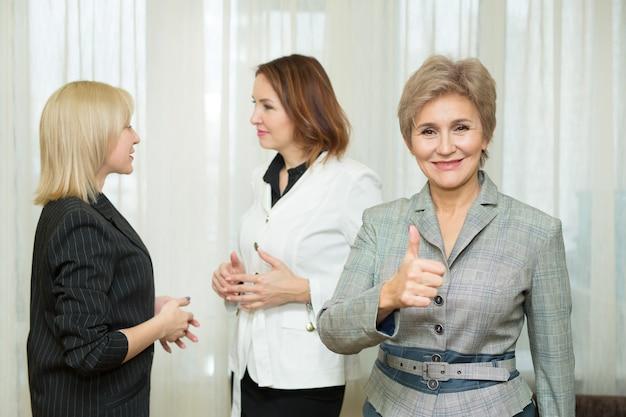 Volwassen vrouw in een pak tegen de achtergrond van haar collega's op kantoor met een handgebaar