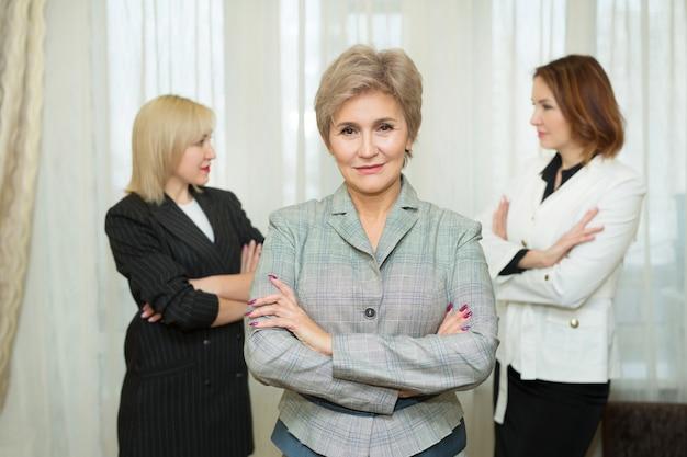 Volwassen vrouw in een pak tegen de achtergrond van haar collega's op kantoor