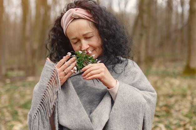 Volwassen vrouw in een voorjaar bos