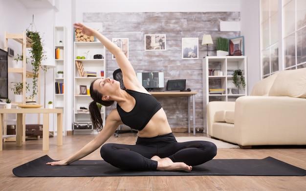 Volwassen vrouw in fitnesslegging die yoga op mat in huis doet. lotus yoga houding.