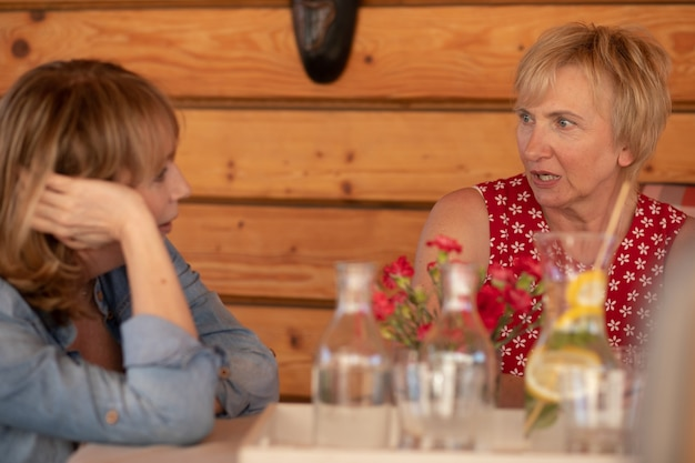 Volwassen vrouw in gesprek met vriend, gezondheidsprobleem, relatieondersteuning, zorg.