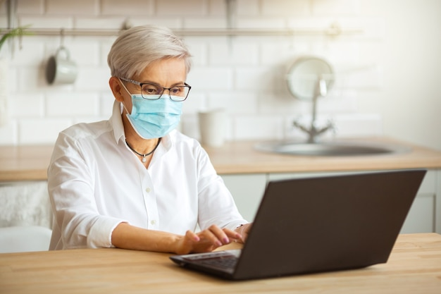Volwassen vrouw in glazen en in een medische jurk aan tafel met een laptop