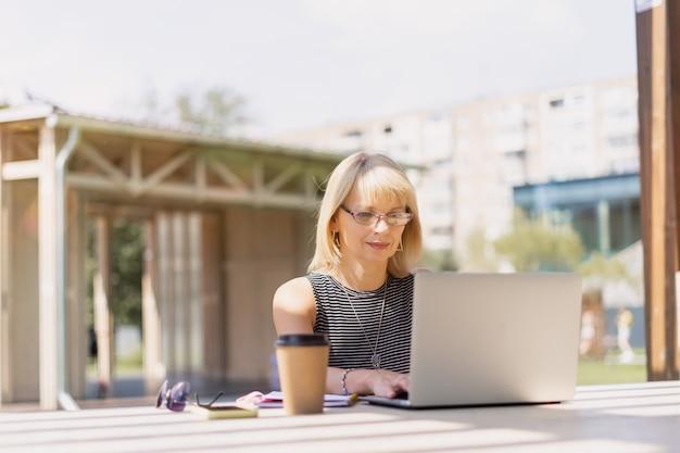 Volwassen vrouw in glazen met laptop