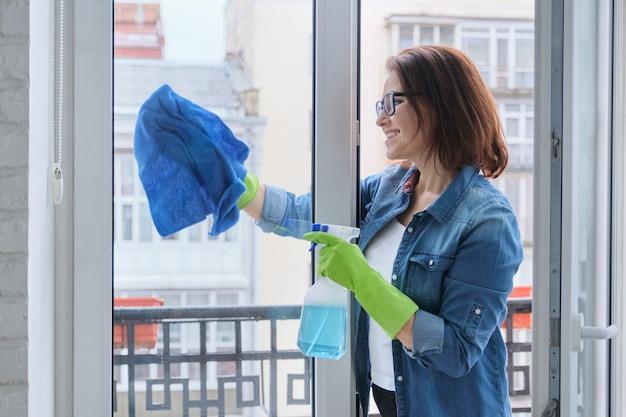 Volwassen vrouw in handschoenen met microfiber doek bespoten met afwasmiddel reinigt glazen raam in kamer