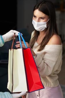 Volwassen vrouw in quarantaine met gezichtsmasker krijgt eten thuisbezorgd