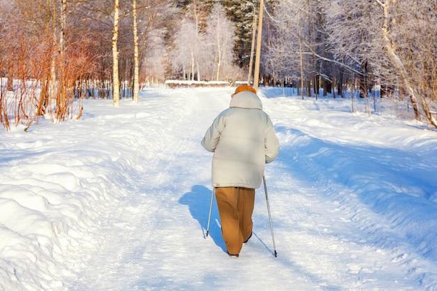 Volwassen vrouw in wintersportkleding met stokken voor nordic walking op winterlandschap stadspark