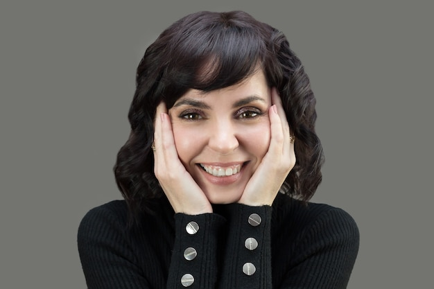 Volwassen vrouw in zwarte trui met kort haar. open brede glimlach