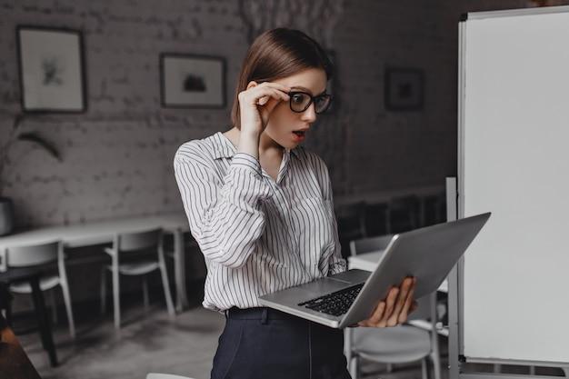 Volwassen vrouw kijkt in shock naar laptop, haar bril van verbazing opstijgen. portret van werknemer in zwart-wit outfit in kantoor.