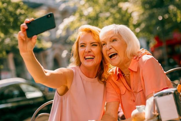 Volwassen vrouw lacht en neemt spannende selfies met haar vrolijke oude moeder