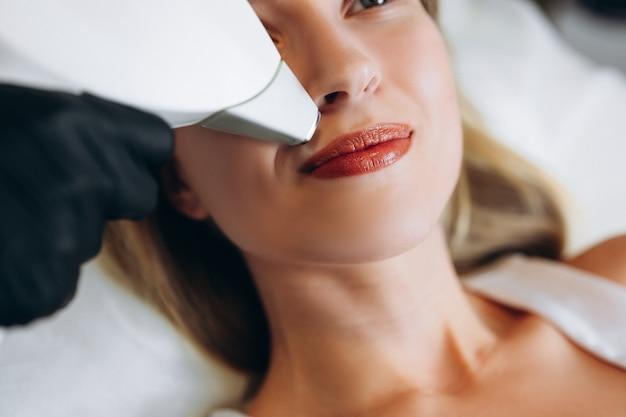 Volwassen vrouw liggend op medische tafel in schoonheidskliniek, met laser ontharing in professionele schoonheidssalon. vrouwelijke schoonheidsspecialist in uniform met behulp van machine voor laser ontharing.