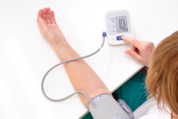 Volwassen vrouw meet bloeddruk, witte achtergrond. arteriële hypotensie.