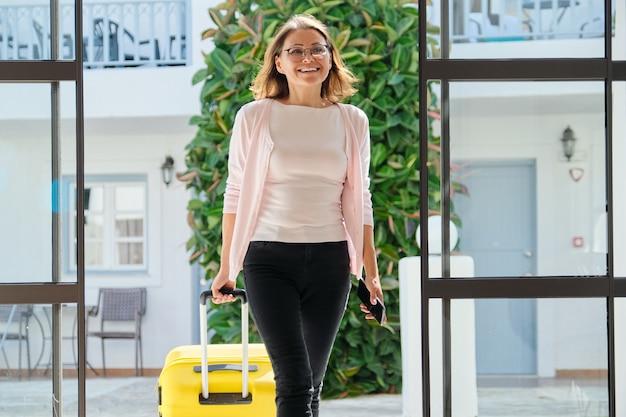 Volwassen vrouw met bagage met koffer die naar de hotellobby gaat, vrouw die met zakenreis reist