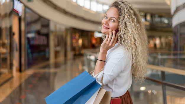 Volwassen vrouw met boodschappentassen in het winkelcentrum
