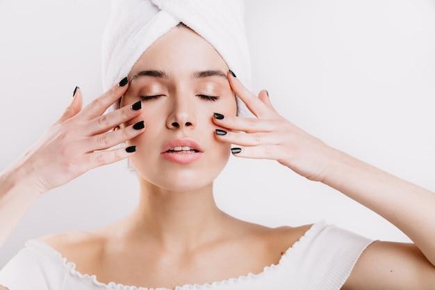 Volwassen vrouw met een gezonde huid masseert haar gezicht om de jeugd te verlengen. momentopname van meisje na douche op geïsoleerde muur.