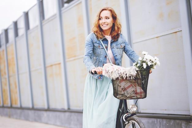 Volwassen vrouw met fiets in de stad