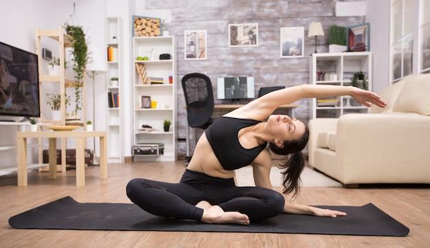 Volwassen vrouw met gesloten ogen zittend op yoga pose in huis haar rug uitrekken.