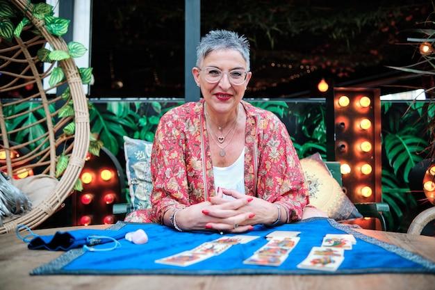 Volwassen vrouw met grijs haar die tarotkaarten gebruikt om de toekomst te voorspellen