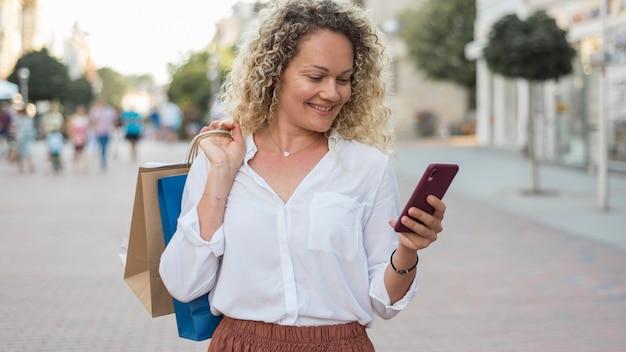 Volwassen vrouw met krullend haar met boodschappentassen