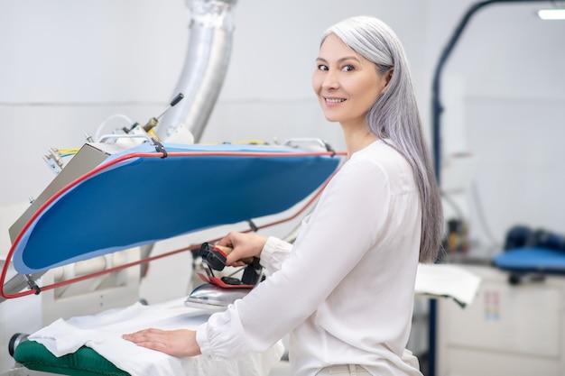 Volwassen vrouw met lang grijs haar doet stomerij kleren stomen in goed humeur