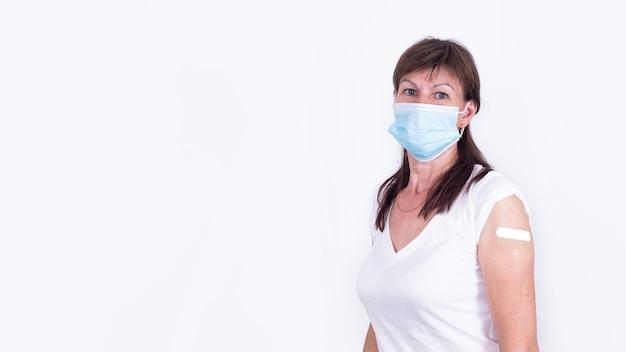 Volwassen vrouw met masker met pleister op schouder na vaccinatie tegen coronavirus of griep verplicht