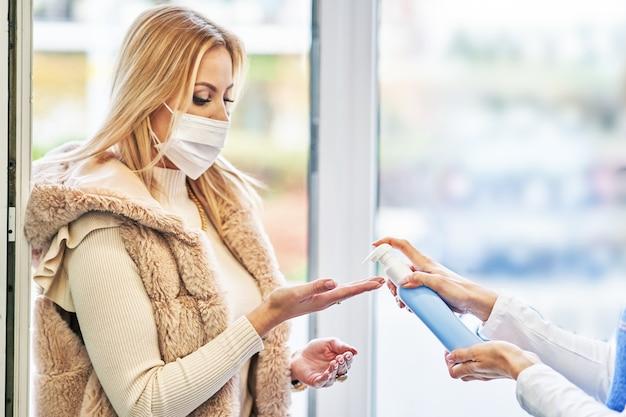 Volwassen vrouw met medisch masker handen ontsmetten voordat ze de supermarkt binnengaat